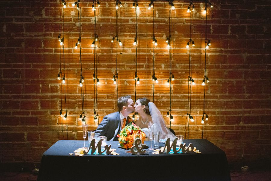 Bride and Groom Kissing at Sweetheart Table with Brick Walls and String Light Backdrop | Downtown St. Pete Wedding Venue NOVA 535 Event Space
