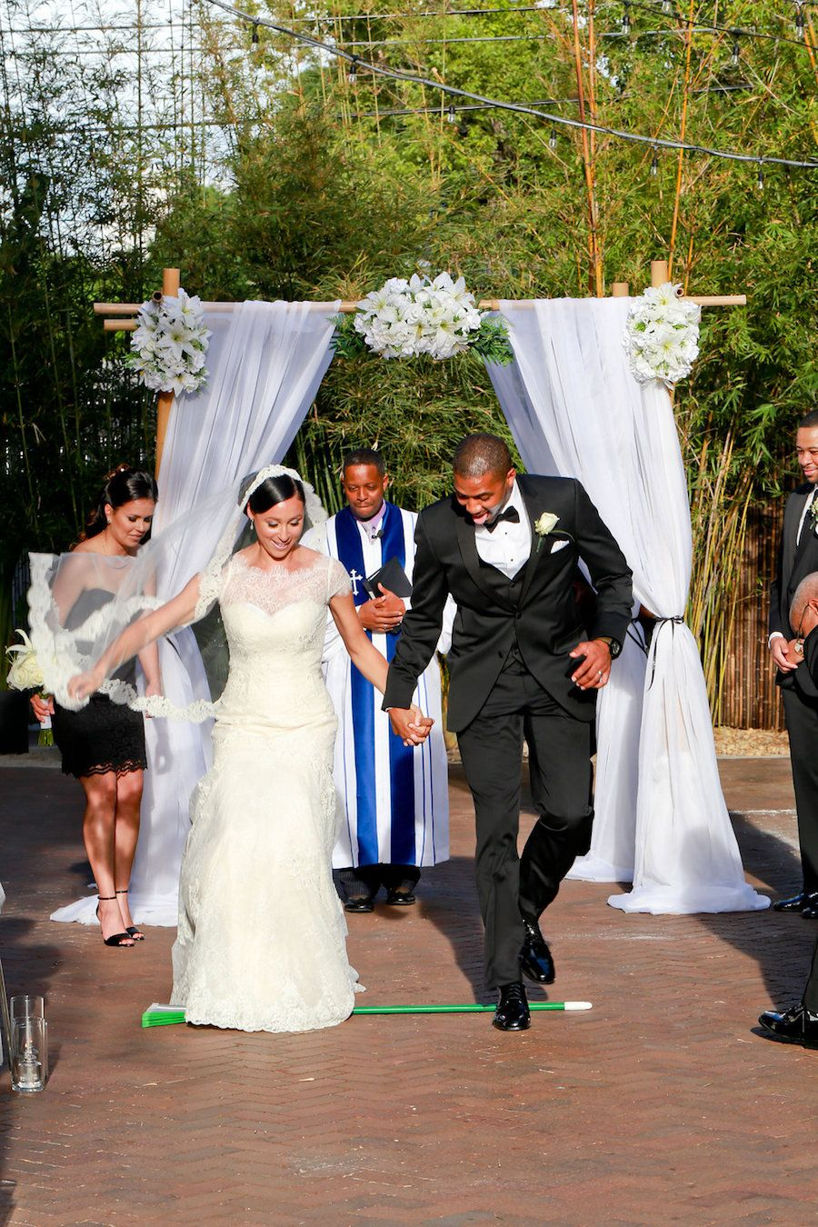 Bride and Groom Jumping the Broom during Outdoor Wedding Ceremony in Bamboo Garden | Outdoor downtown St. Petersburg wedding Venue NOVA 535