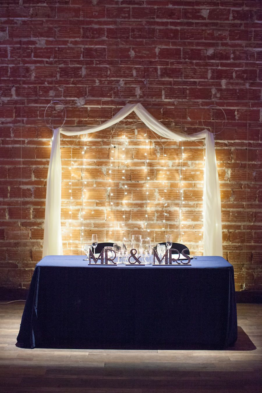 Bride and Groom Sweetheart Table with Exposed Brick Wall Backdrop at Modern, Downtown St. Pete Wedding Venue NOVA 535 for a romantic st. petersburg wedding