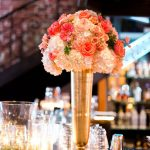 St. Pete Wedding Reception Table Decor with Candlelight and Ivory and Coral Bouquet of Flowers in Tall Gold Centerpieces