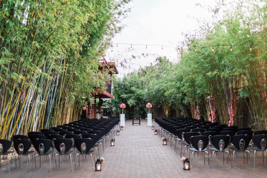 St. Petersburg Outdoor Wedding Ceremony with Black Chairs and Ivory and Coral Floral Centerpieces | St. Pete Wedding and Event Space NOVA 535