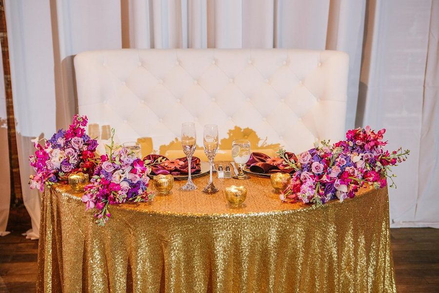 Bride and Groom Sweetheart Table with Purple and Fuchsia Wedding Centerpieces on Gold Sequin Specialty Linens at St Pete Wedding Venue NOVA 535 | Purple Orange and Turquoise Moroccan Inspired St. Pete Wedding