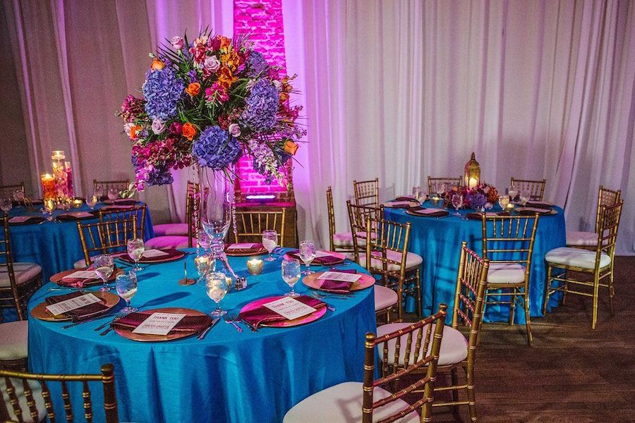 Wedding Reception with Gold, Purple, Orange and Teal Centerpieces with Gold Chiavari Chairs and Table Settings at St. Petersburg Wedding Venue NOVA 535 | Purple Orange and Turquoise Moroccan Inspired St. Pete Wedding