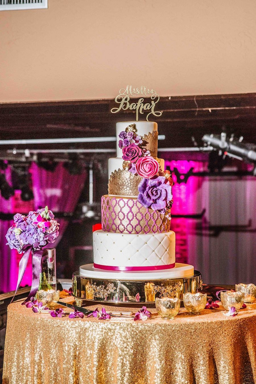 Four Tier Round Gold, Pink and Purple Wedding Cake and Gold Sequin Name Cake Topper on Gold Sequined Specialty Linen at Downtown St. Pete Wedding Reception Venue NOVA 535 | Purple Orange and Turquoise Moroccan Inspired St. Pete Wedding