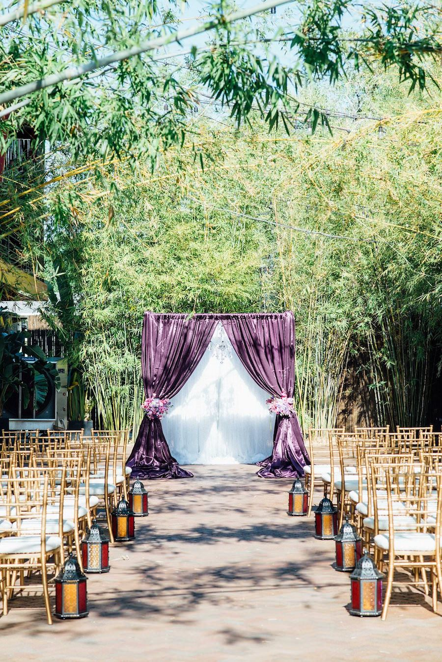Outdoor Wedding Ceremony at St Pete Wedding Venue NOVA 535 with Purple Linen Flocked Archway and Gold Chiavari Chairs