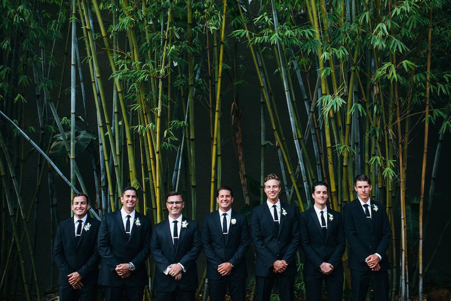 Groom and Groomsmen Wedding Day Portrait in All Black Tuxes with Black Skinny Ties | Outdoor Bamboo Courtyard Downtown St. Pete Wedding Venue NOVA 535