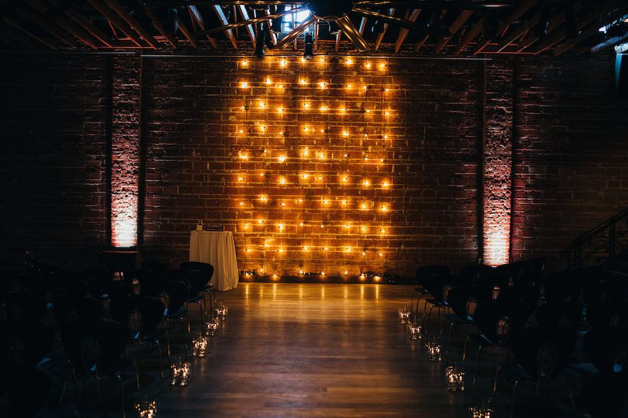 Modern, Industrial Wedding Ceremony with Lighted Backdrop Decor Against Brick Wall | Downtown St. Pete Wedding Venue NOVA 535