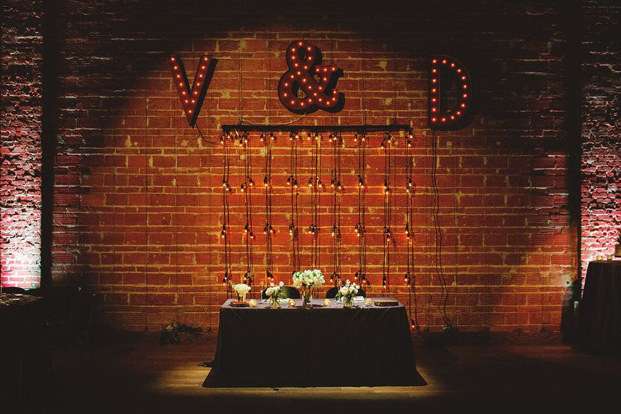 Bride and Groom Sweetheart Table with Lighted Marquee Monogram Letters, Exposed Brick and Industrial String Lights | Modern Industrial Wedding Reception Decor Inspiration | Downtown St. Petersburg Wedding Venue NOVA 535