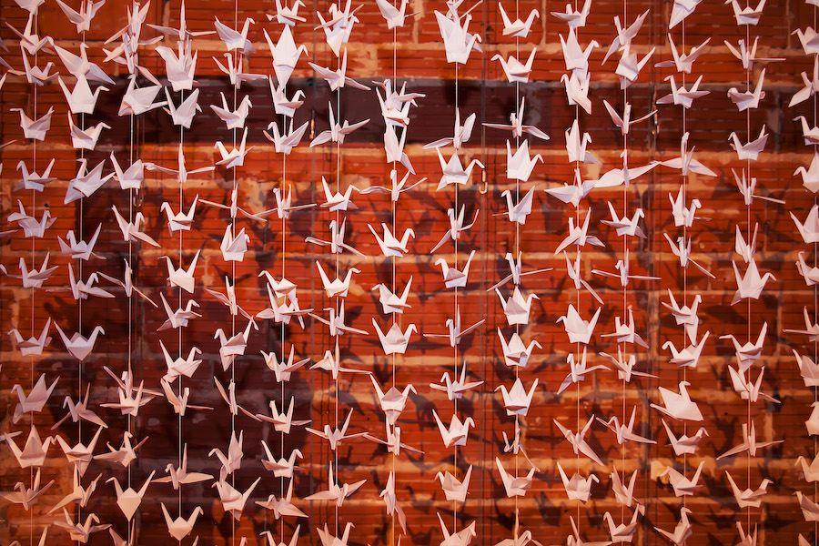 Paper Crane Wedding Ceremony Backdrop Against Exposed Brick Wall | Modern, Unique Wedding Ceremony Ideas