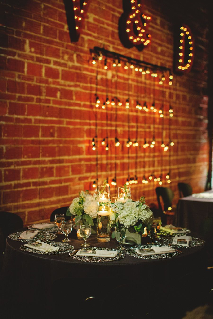 Silver and Ivory Wedding Reception Decor Centerpieces with Floating Candles, Silver Chargers and Exposed Brick Walls with Hanging String Lights