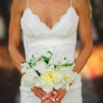 Bridal Wedding Portrait in Ivory Lace Katie May Wedding Dress with Spaghetti Straps and Elegant Ivory Wedding Bouquet of Ivory Peonies and Greenery