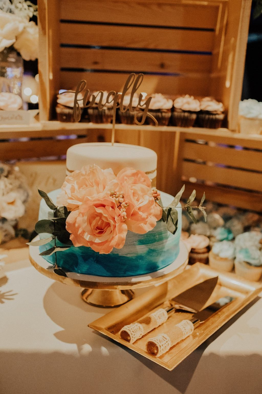 Rustic Modern Wedding Reception at historic DTSP venue NOVA 535 gorgeous Dessert Table with Blue and Pink Floral Round Two Tiered Wedding Cake on Gold Cake Stand and Finally Stylish Gold Cake Topper with Rustic Wooden Crates and Cupcakes | pink boho chic
