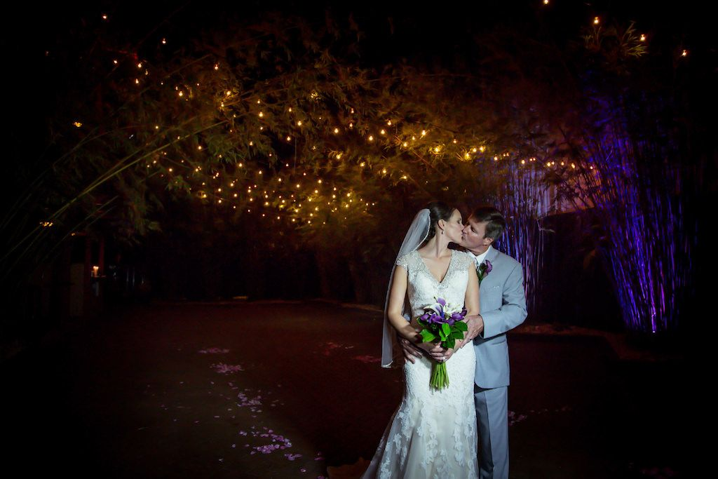 Nighttime Outdoor Bride and Groom Portrait at DTSP Wedding Venue NOVA 535 Bamboo Garden with Purple and Greenery Bouquet and Boutonnière, Groom in Gray Suit