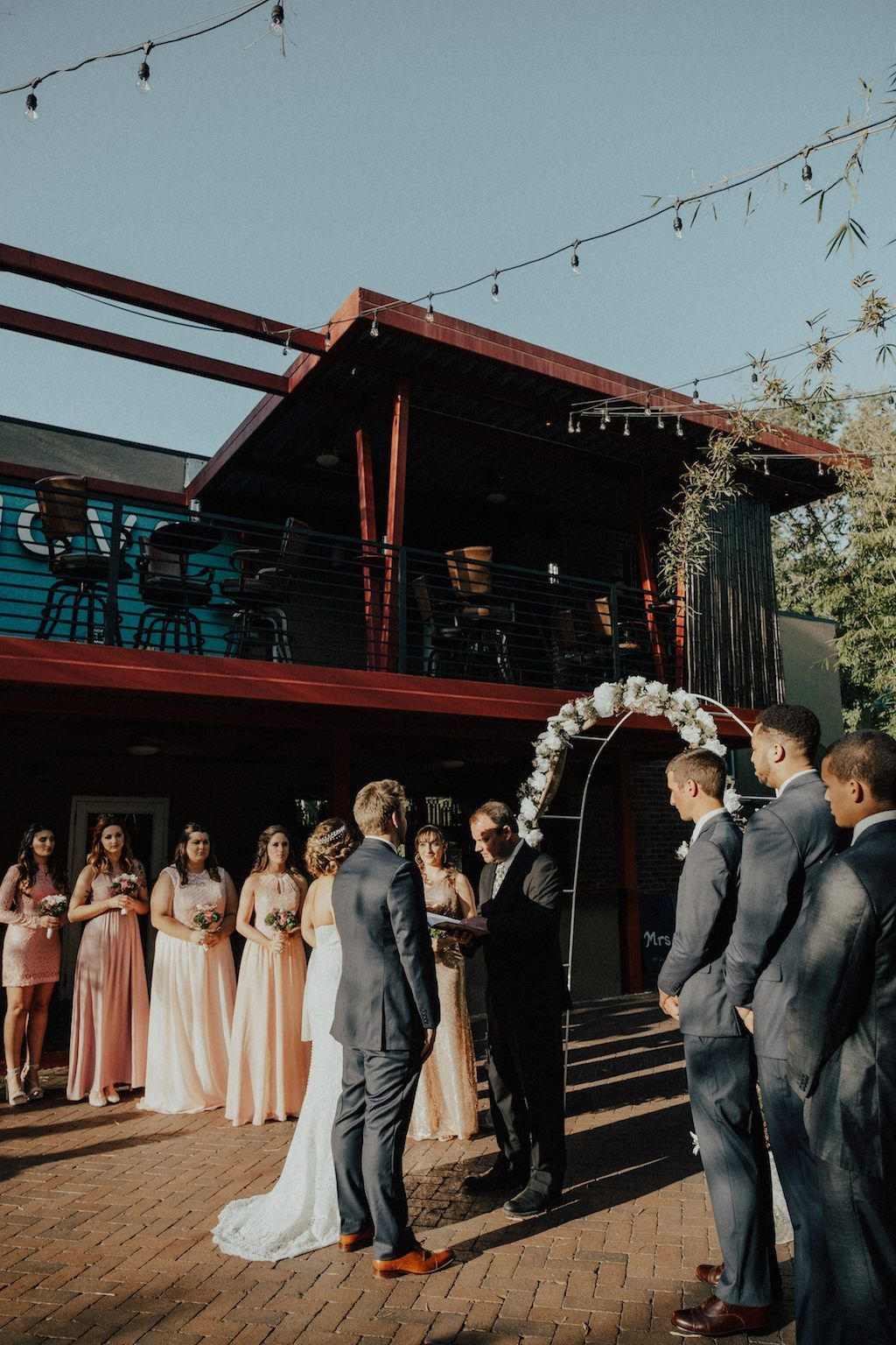Bamboo Outdoor Courtyard Garden Wedding Ceremony Portrait, Groomsmen in Gray Suits, Bridesmaids in Mismatched Blush and Cream Dresses, with White Floral and Greenery Arch | Downtown St Pete Wedding Venue NOVA 535