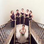 Modern Bridal Party Portrait, Bride in Allure Wedding Dress with Mismatched Bill Levkoff Plum Bridesmaids Dresses, and with Purple and White Bouquets with Greenery on Copper Staircase | Plum and Silver Wedding at Downtown St Pete Historic Wedding Venue NOVA 535
