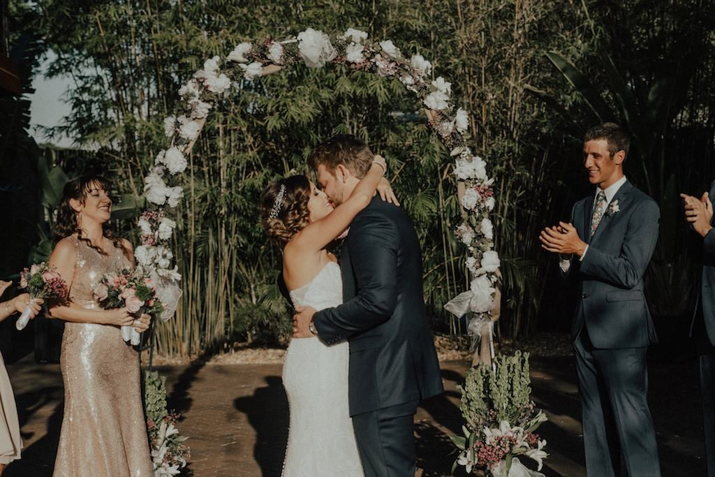 Bamboo Outdoor Courtyard Garden Wedding Ceremony Portrait, Groomsmen in Gray Suits with Floral Tie, Bridesmaids in Mismatched Blush and Rose Gold Dresses, with Rustic Bohemian Floral White Floral and Greenery Arch | Downtown St Pete Wedding Venue NOVA 535