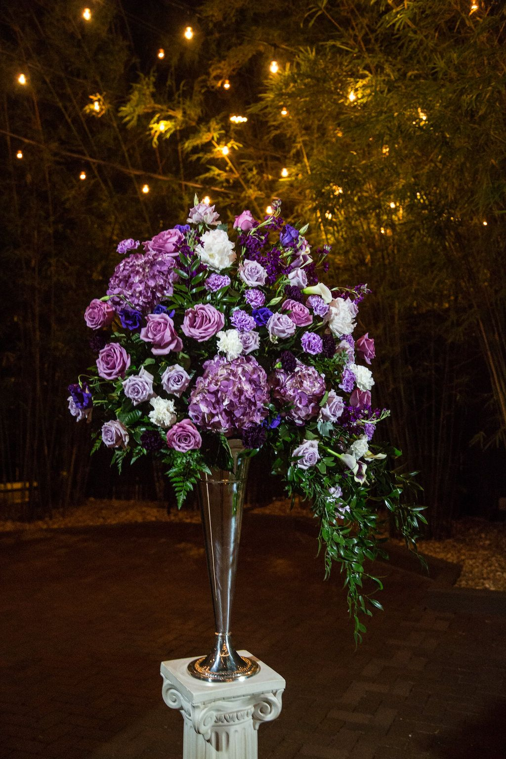 Tall Purple White and Plum Rose Wedding Flowers with Fern Greenery in Tall Silver Vase