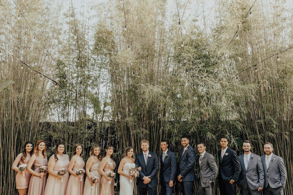 Outdoor Bamboo Garden Wedding Party Portrait, Groomsmen in Mismatched Gray Suits with Floral Ties, Bridesmaids in Mismatched Rose Gold, Blush, and Pink Dresses with Pink and White Floral Bouquets | Downtown St Petersburg Wedding Ceremony Venue NOVA 535