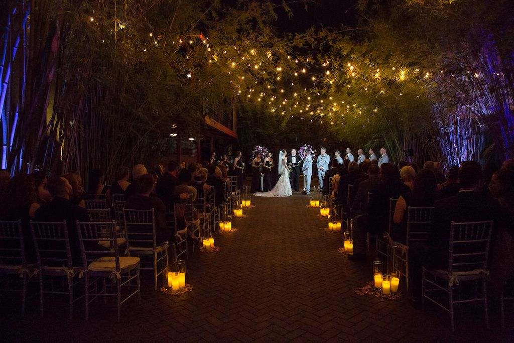 Outdoor Brick Courtyard Wedding Nighttime Ceremony Portrait With Hurricane Candle Lanterns Silver Chiavari Chairs and String Lights | Bamboo Courtyard Ceremony At Modern St Pete Wedding Venue NOVA 535