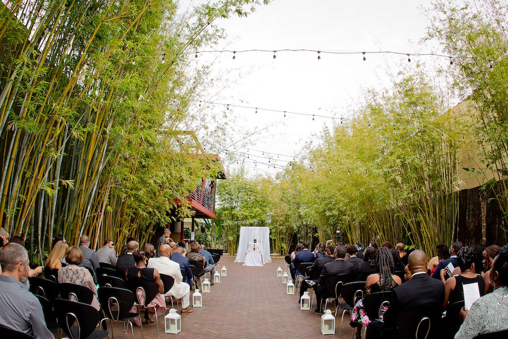 Elegant Black and White Outdoor St. Pete Wedding with Hurricane Lanterns on the Aisle, Bamboo and String Lights, and White Draped Ceremony Arch and Altar | Garden Courtyard Ceremony at Unique Downtown St Pete Venue NOVA 535