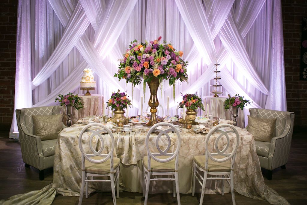 Modern Wedding Reception with Unique Vintage Inspired Furniture and Linens, Tropical Orange, Pink, and Purple Rose with Greenery Centerpieces in Tall Gold Vases, and Drapery with Purple Uplighting | Luxurious St Pete Wedding at Historic Downtown Venue NOVA 535
