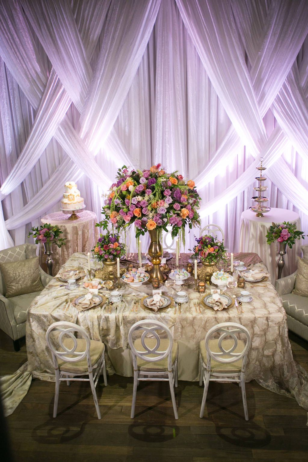 Modern Wedding Reception with Unique Vintage Inspired Furniture and Linens, Tropical Orange, Pink, and Purple Rose with Greenery Centerpieces in Tall Gold Vases, and Drapery with Purple Uplighting | Luxurious St Pete Wedding at Unique Downtown Venue NOVA 535