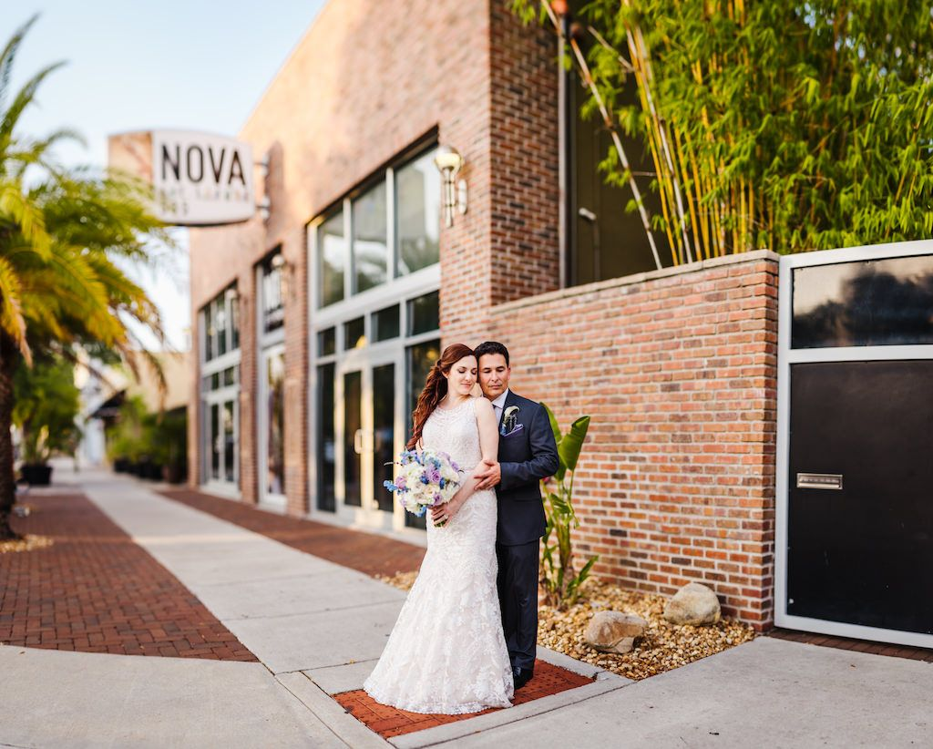 Downtown St Pete Wedding Portrait outside Historic DTSP Wedding Venue NOVA 535, Bride with Blue, Dusty Purple, and White Bouquet