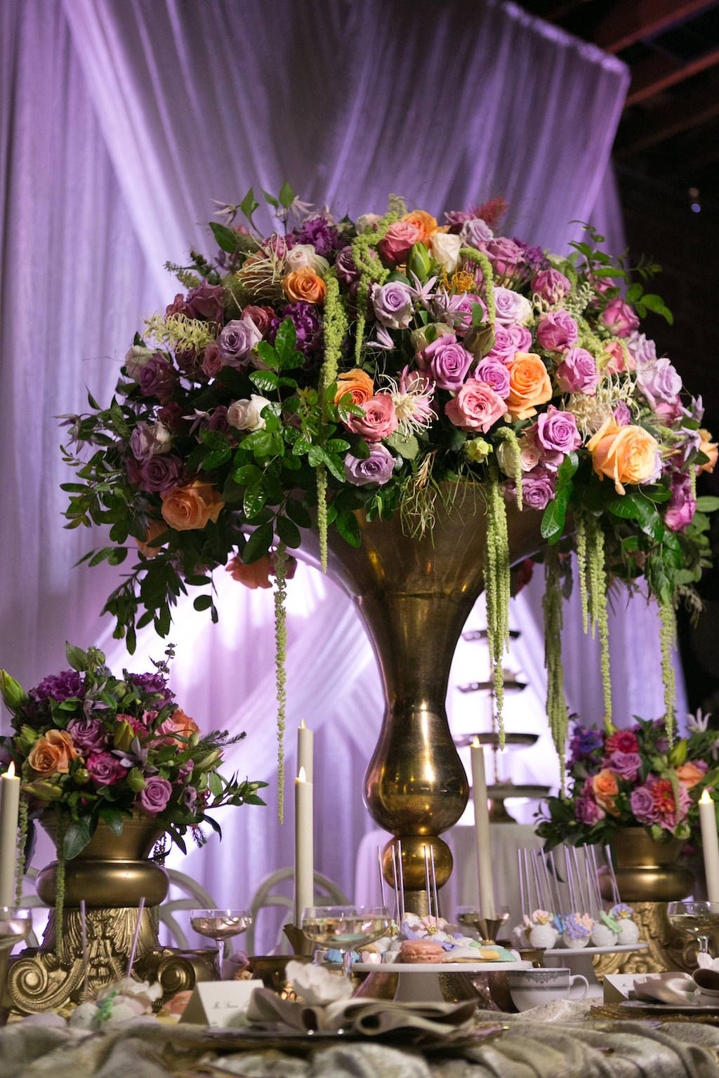 Tall French Inspired Wedding Reception Centerpiece with Pink, Orange, and Purple Roses with Tropical Greenery in Gold Vase | Luxurious St Pete Wedding at Downtown Historic Venue NOVA 535