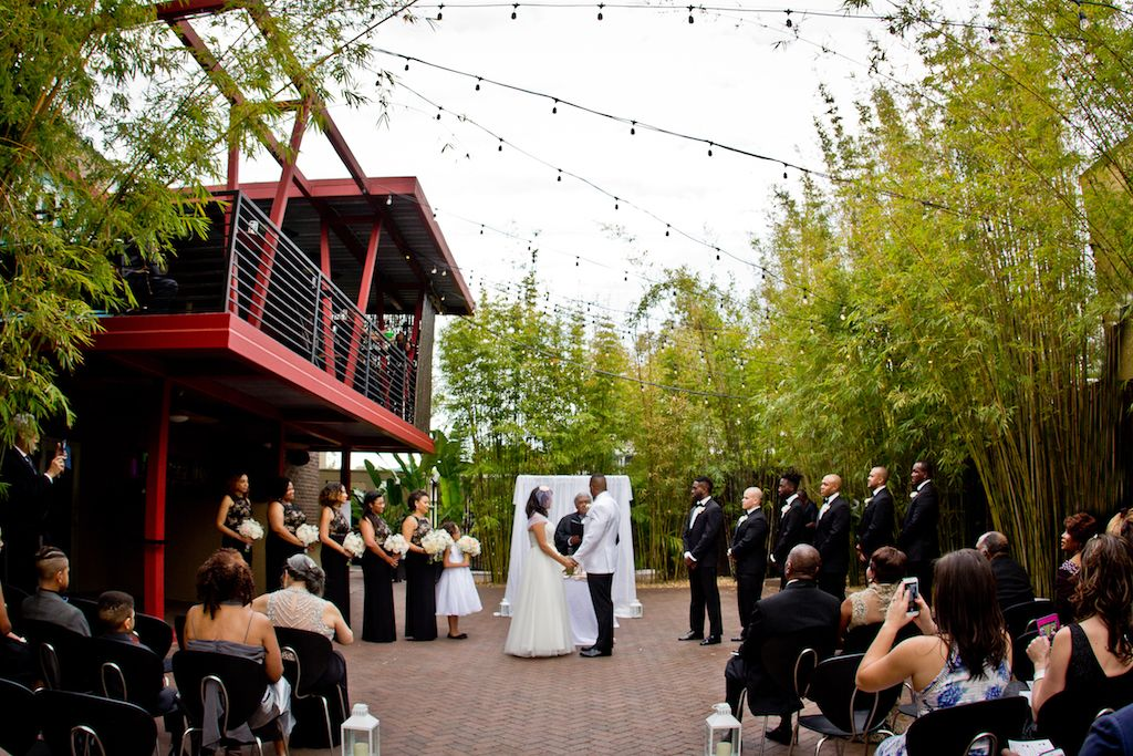 Elegant Black and White Outdoor St Pete Wedding Ceremony Portrait with Hurricane Lanterns on the Aisle, Bamboo and String Lights, and White Draped Ceremony Arch and Altar | Bride Wearing Cap Sleeve Ballgown Dress, Groom in White Jacket with Black Pants, Groomsmen in Black tuxedos, Bridesmaids in Black and Gold Dresses with White Bouquet | Garden Courtyard Ceremony at Unique Downtown St Pete Venue NOVA 535