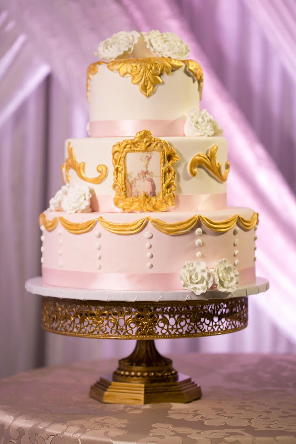 Three Tiered Round Wedding Cake with White Floral and Gold Gilded Frame Mini Portrait and Pink Ribbon Icing Decor on Antique Gold Cake Stand | Luxurious St Pete Wedding at Venue NOVA 535