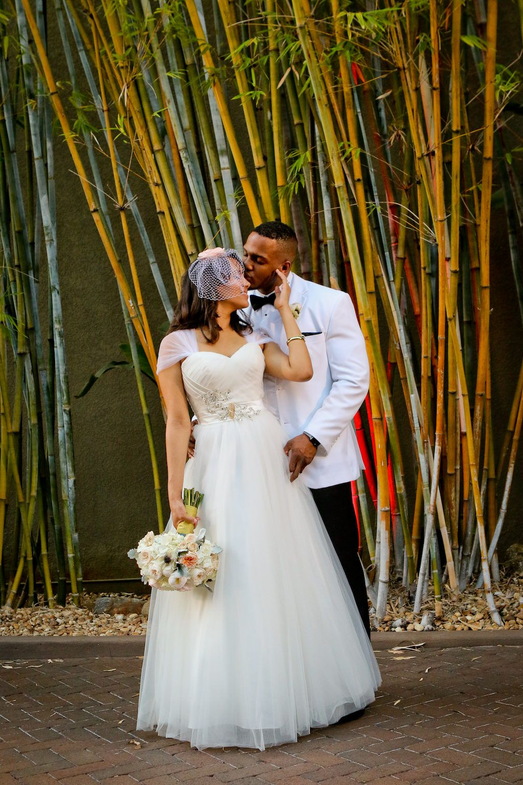 Elegant Black and White Outdoor St Pete Wedding Portrait, Bride in Cap Sleeve Ballgown Dress with Birdcage Veil and White and Pink Floral Bouquet, Groom in White Tuxedo Jacket with Black Pants and Bowtie | Bamboo Garden Courtyard Ceremony at Unique Downtown St Pete Venue NOVA 535Elegant Black and White Outdoor St Pete Wedding Portrait, Bride in Cap Sleeve Ballgown Dress with Birdcage Veil and White and Pink Floral Bouquet, Groom in White Tuxedo Jacket with Black Pants and Bowtie | Bamboo Garden Courtyard Ceremony at Unique Downtown St Pete Venue NOVA 535