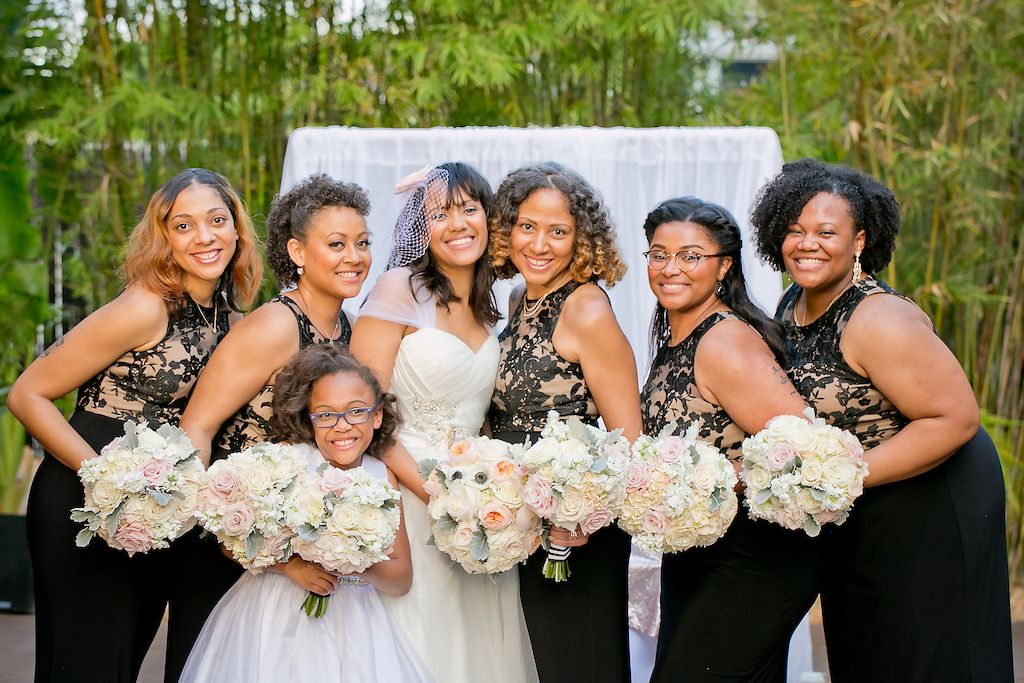 Elegant Black and White Outdoor St. Pete Wedding Bridal Party Portrait, Bride in Princess Neckline Cap Sleeve Dress with Birdcage Veil, Bridesmaids in Black and Tan Floral Dress with Long Black Skirt, with Pastel Pink, White Floral and Greenery Bouquets | Bamboo Garden Courtyard Ceremony at Unique Downtown St Pete Venue NOVA 535
