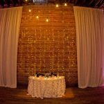 Elegant Black and White St Pete Wedding Reception Sweetheart Table with Textured Linen, White Draping, Hanging String Edison Lights on Exposed Brick Wall and Votive Candles | Unique Downtown St Pete Wedding Venue NOVA 535
