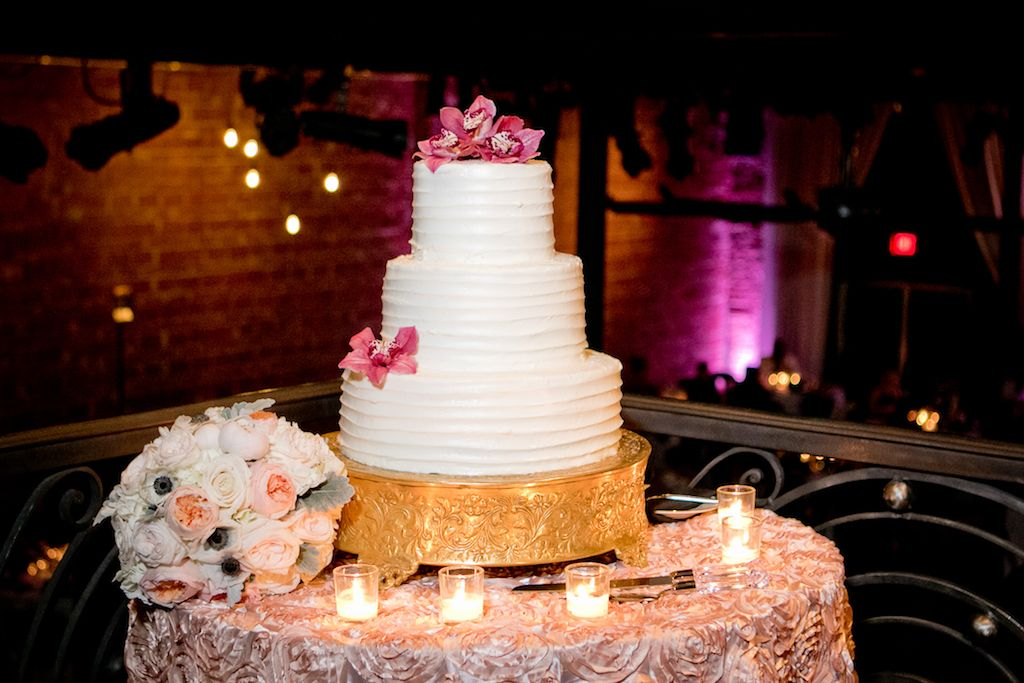 Elegant Black and White St Pete Wedding Reception Dessert Table with Three Tier Round White Cake with Pink Flowers on Gold Cake Stand, with Blush, Anemone, and White Rose Bouquet with Greenery, Votive Candles, and Textured Linen | Unique Downtown St Pete Wedding Venue NOVA 535