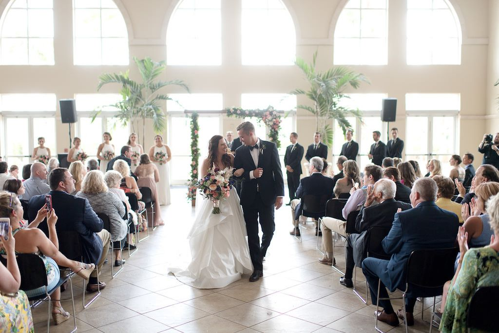 Indoor Church Ceremony Exit Portrait with Floral Arch with Peach Roses, White and Purple and Pink Flowers with Greenery, and Palm Trees | Lutz FL Wedding Ceremony Venue Idlewild Baptist Church