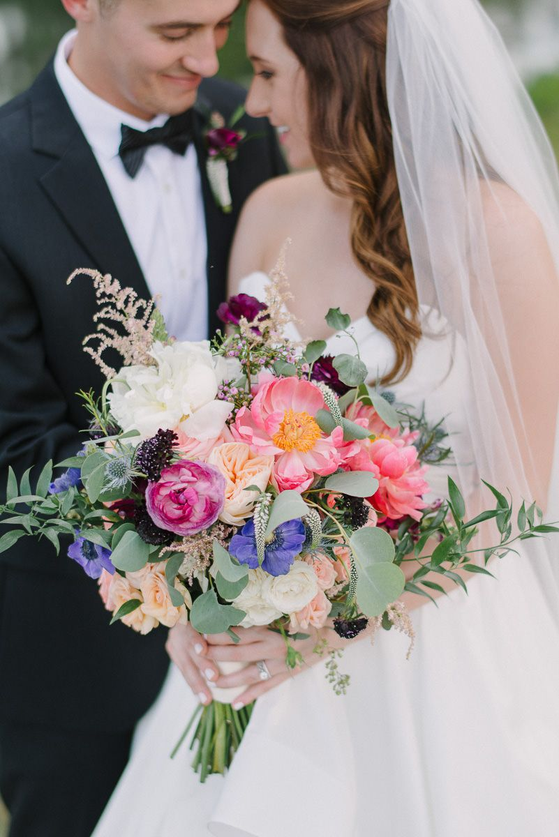 Outdoor Bride and Groom Portrait, with Pink, Peach, Purple, White Floral and Greenery Bouquet, Groom in Black Tux with Red Flower Boutonniere