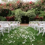 Outdoor Garden Wedding Ceremony Decor with White Folding Chairs with Pink and White Flowers, Pearl Beads, and Gold Ribbon | St Pete Wedding Ceremony Venue The Sunken Gardens