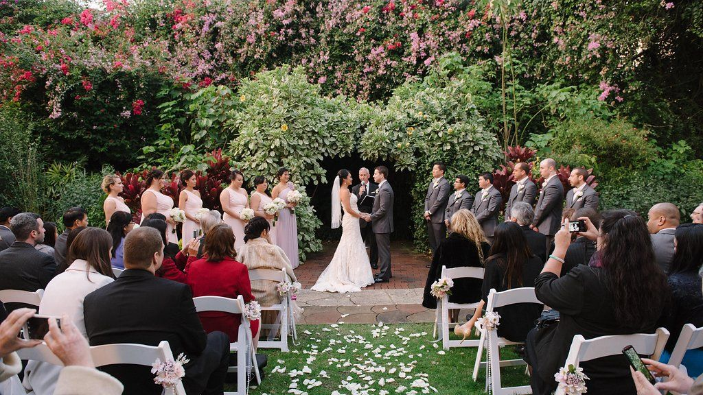 Outdoor Garden Wedding Ceremony Portrait, with White Folding Chairs with Pink and White Flowers, Pearl Beads, and Gold Ribbon, Bridesmaids in Off the Shoulder Blush PInk Dresses, Groomsmen in Gray Suits | St Pete Wedding Ceremony Venue The Sunken Gardens