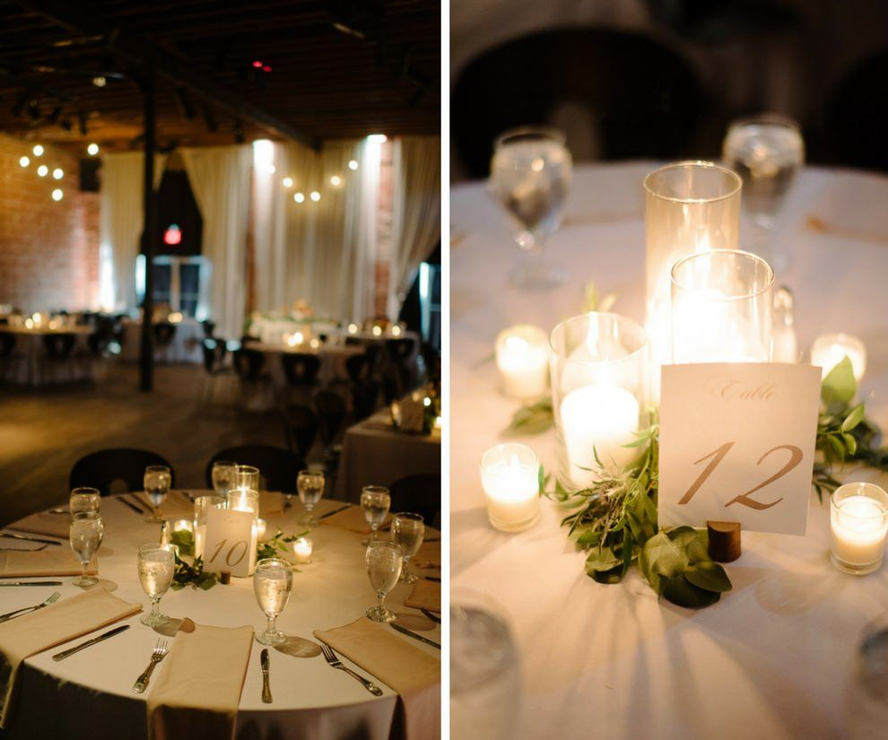 Candlelit St. Pete Wedding Reception with Champagne and White Linens, Pillar Candles in Glass Holders with Greenery Centerpiece and Gold Printed Paper Table Number Card, Hanging Edison Bulb String Lights | Downtown St Pete Unique Wedding Venue NOVA 535