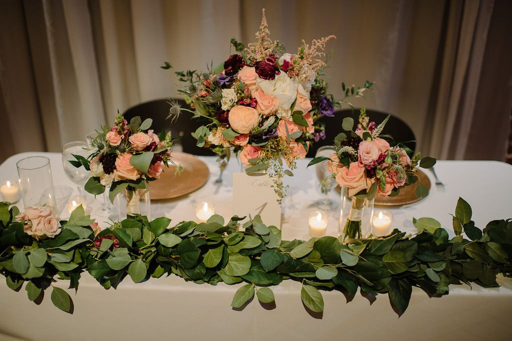 St. Pete Wedding Reception Sweetheart Table with Greenery Garland, and Peach Rose, Pink, White, Magenta, and Purple Flowers with Greenery Low Centerpiece in Glass Vase with Gold Chargers