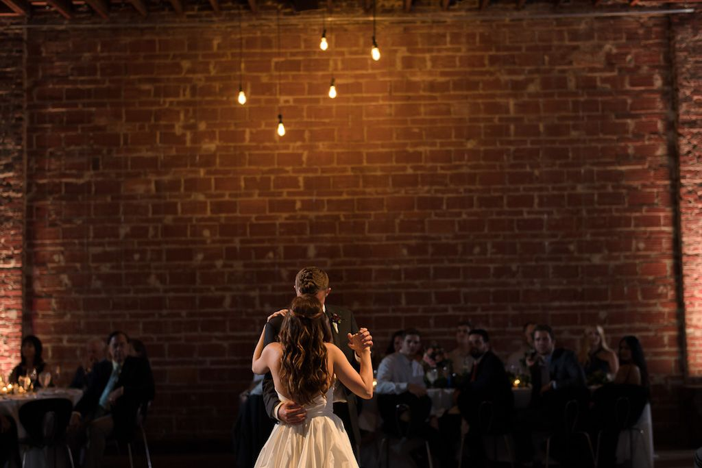 St. Pete Wedding Reception First Dance Portrait with Exposed Brick Wall and Hanging Edison Bulb Lights | Unique Downtown St Pete Wedding Venue NOVA 535  St. Pete Wedding Reception