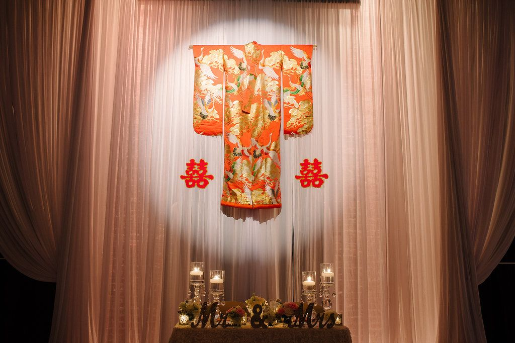 Multicultural St. Pete Wedding Reception Sweetheart Table with Hanging Traditional Chinese Wedding Dress and Characters, White Draping, Oversized Votive Candles in Glass Holders and Mr and Mrs Signs | Downtown St Pete Wedding Reception Venue NOVA 535