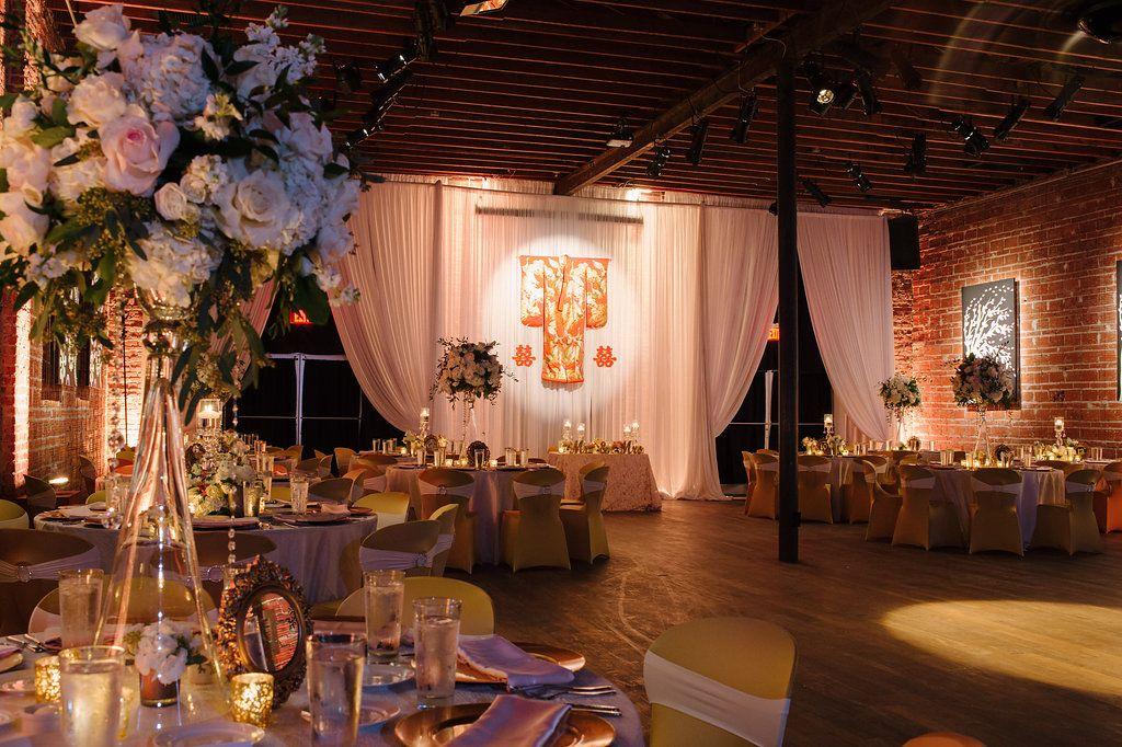Gold and Pink Multicultural St. Pete Wedding Reception with White Draping, Hanging Traditional Chinese Wedding Dress and Characters, Round Tables with Satin Linens, Gold Fabric Covered Chairs, Extra Tall Pink FLoral and Greenery Centerpieces in Glass Vases with Hanging Jewels | Downtown St Pete Unique Wedding Reception Venue NOVA 535