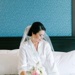 Bride Getting Ready Hotel Interior Portrait, with White and Pink Bouquet and Comb Veil in White Silk Robe