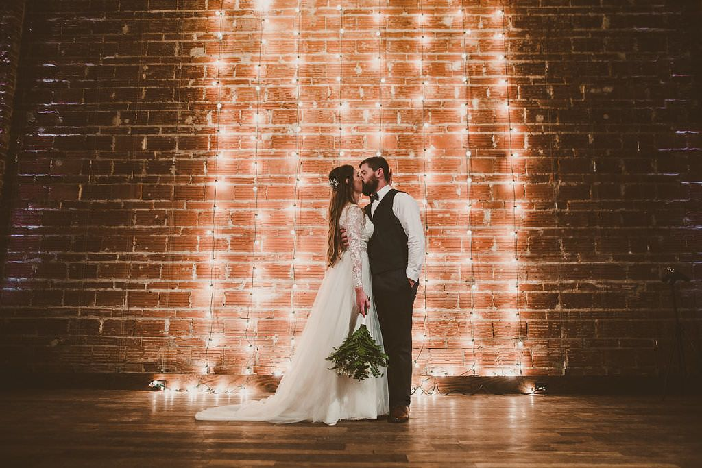 Modern string light ceremony backdrop in front of exposed brick wall at St. Pete wedding venue Nova 535