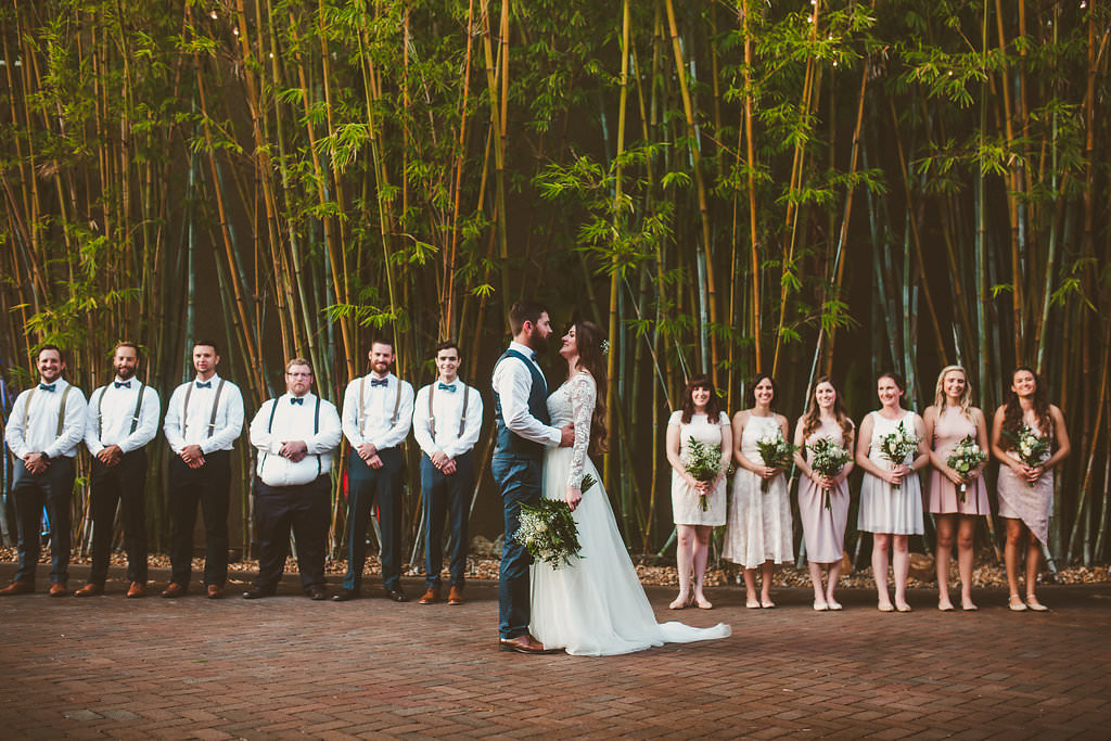 Bridal party with bridesmaids in mismatched pink dresses with groomsmen in bow ties in front of modern bamboo garden at St Pete wedding venue Nova 535