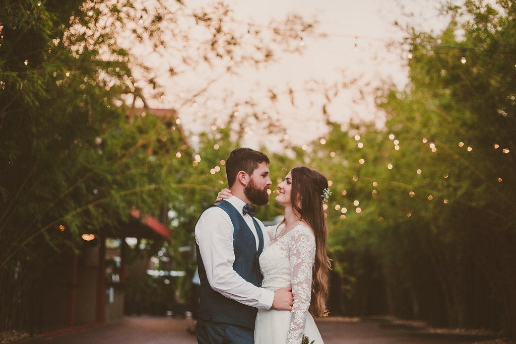 Bride in long sleeve lace wedding dress with groom in dark gray vest and bow tie surrounded by bamboo at modern St Pete wedding venue Nova 535