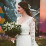 Bride in long sleeve lace wedding dress with neutral greenery bouquet in front of modern St Pete mural wall