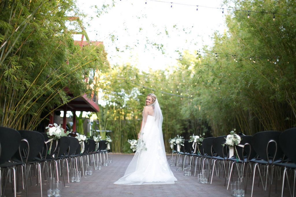 Bride with chapel veil at modern ceremony under string lights in bamboo garden at NOVA 535