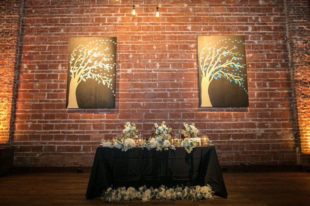 Sweetheart table with classic white and green florals at modern industrial venue NOVA 535